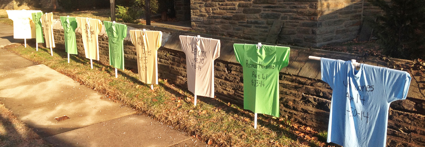Memorial for victims of gun violence, with T-shirts displaying victims' names, ages, and date of death.