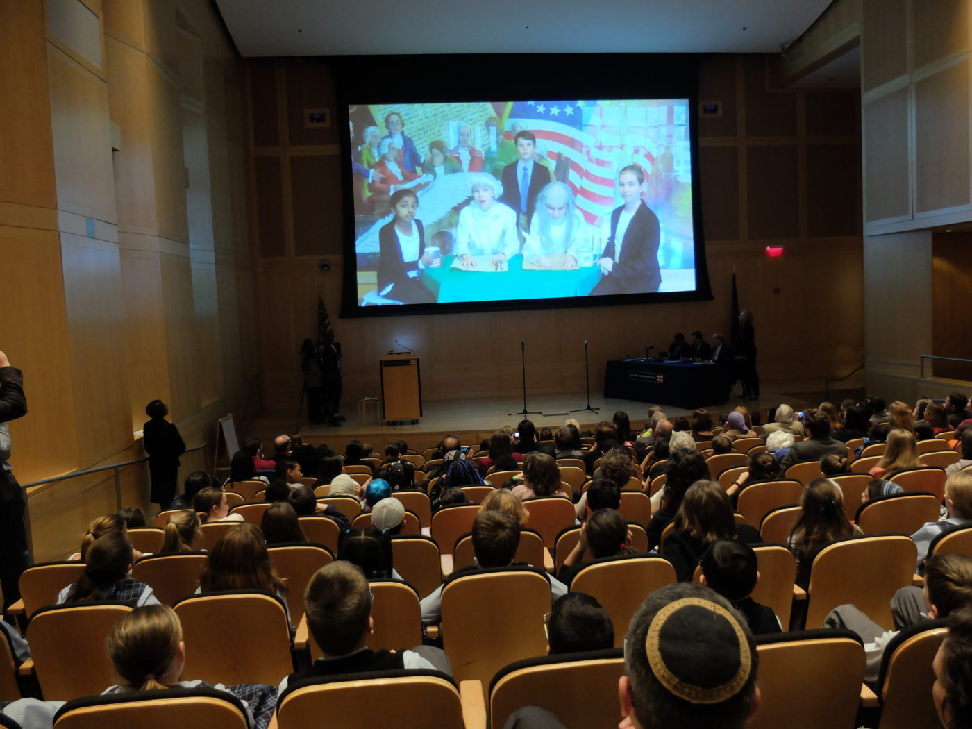 Audience watches a video made by one of the classes.