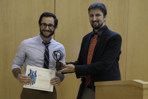 Postdoctoral fellow Matt Motta (left) accepts the Elsevier Atlas award.