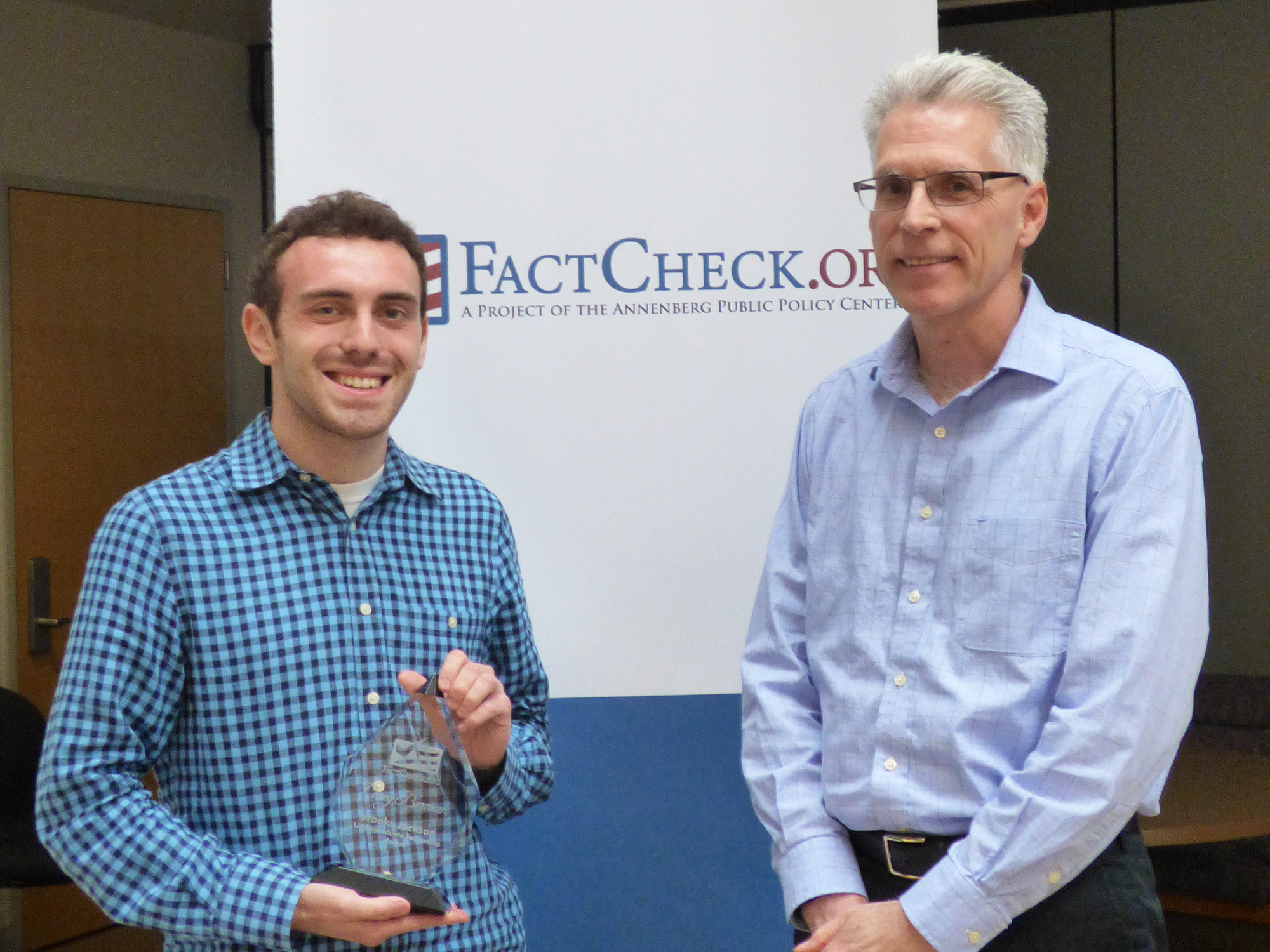 Corey Berman (left), holding the Brooks Jackson Undergraduate Fellowship Award, and FactCheck.org director Eugene Kiely.