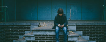 Young teenager sits alone looking down at their smartphone. Credit: Gaelle Marcel/Unsplash.