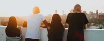 4 teens stand with their backs to the camera looking out towards a sunny city skyline. Slider art for study on 13 Reasons Why and adolescent suicide.